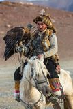哈萨克人与马的老鹰猎人Berkutchi,当寻找对与的野兔在他的胳膊时的鹫 免版税库存图片