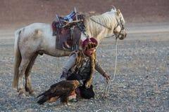 哈萨克人与马的老鹰猎人Berkutchi,当寻找对与的野兔在他的胳膊时的鹫 库存图片