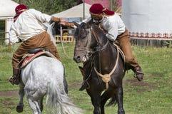 哈萨克人人在哈萨克斯坦做传统游牧武器角力在他们的马, 库存照片