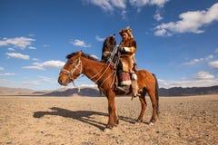 哈萨克人在传统衣物的老鹰猎人,在马背上,当寻找对拿着在他的胳膊时的野兔一只鹫 免版税库存照片