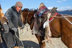 哈萨克人在传统衣物的老鹰猎人,在马背上,当寻找对拿着在他的胳膊时的野兔一只鹫 库存照片