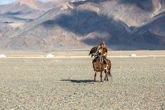 哈萨克人在传统衣物的老鹰猎人,在马背上,当寻找对拿着在他的胳膊时的野兔一只鹫 免版税图库摄影