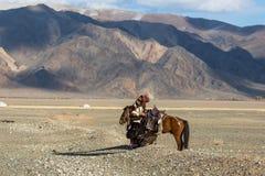 哈萨克人在传统衣物的老鹰猎人,在马背上,当寻找对拿着在他的胳膊时的野兔一只鹫 免版税库存图片