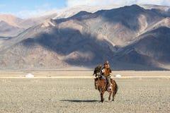哈萨克人在传统衣物的老鹰猎人,在马背上,当寻找对拿着在他的胳膊时的野兔一只鹫 库存图片