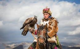 哈萨克人在他的马的老鹰猎人 免版税库存图片