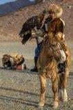 哈萨克人妇女老鹰猎人传统衣物,当寻找对拿着在他的胳膊时的野兔一只鹫 免版税库存图片