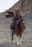 哈萨克人老鹰猎人传统衣物,当寻找对拿着一只鹫时的野兔 免版税库存照片