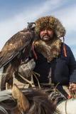 哈萨克人老鹰猎人传统衣物,当寻找对拿着在他的胳膊时的野兔一只鹫 免版税库存图片
