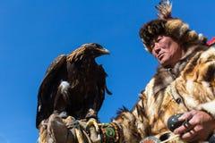 哈萨克人老鹰猎人传统衣物,当寻找对拿着在他的胳膊时的野兔一只鹫 免版税库存照片