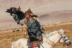 哈萨克人老鹰猎人传统衣物,当寻找对拿着在他的胳膊的野兔一只鹫在韦斯特时沙漠山  免版税库存图片