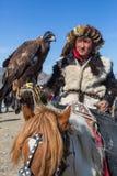 哈萨克人老鹰猎人传统衣物,有在他的胳膊的一只鹫的在与鸟的每年全国竞争时 免版税库存图片