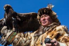 哈萨克人老鹰猎人传统衣物,有在他的胳膊的一只鹫的在与鸟的每年全国竞争时 库存照片