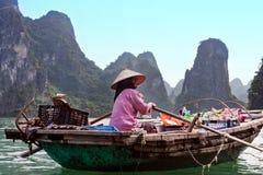 哈隆,越南- 2011年10月30日:妇女在Kua浮动村庄卖在一条小船的食物苍白在Daw附近顾海岛  免版税库存照片