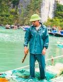 哈隆,越南- 2016年12月16日:海湾的一个人卖鱼 垂直 复制文本的空间 库存照片