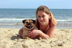 哈巴狗狗和所有者在一个晴朗的海滩 免版税图库摄影