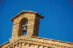 响铃和在城市墙壁和塔的圣的蓝色晴朗的天空看法在砖教会顶部的与树在日落在圣吉米尼亚诺 免版税库存照片