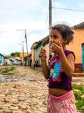响铃convento古巴de弗朗西斯科iglesia市长广场圣塔特立尼达y 2016年6月:哄骗使用与在街道上的铅笔的女孩,在城市的最恶劣的边 免版税库存图片