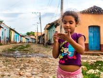 响铃convento古巴de弗朗西斯科iglesia市长广场圣塔特立尼达y 2016年6月:哄骗使用与在街道上的铅笔的女孩,围拢由特立尼达的色的房子 免版税库存照片