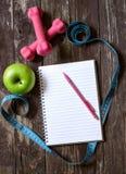 哑铃、卷尺和健康食物在木桌 图库摄影