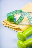 哑铃、苹果、毛巾和一个瓶水 免版税库存照片