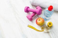 哑铃、水、毛巾、苹果和卷尺 免版税库存图片
