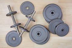 哑铃和自由重量在木地板上 免版税库存照片