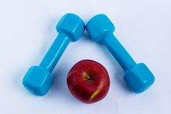 哑铃和苹果白色背景体育 免版税库存图片