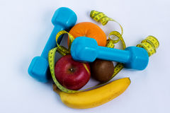 哑铃和苹果,桔子,香蕉,猕猴桃白色背景 免版税库存图片