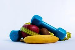 哑铃和苹果,桔子,香蕉,猕猴桃白色背景 库存照片