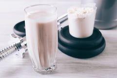 哑铃和蛋白质在白色木桌上的玻璃震动 库存图片