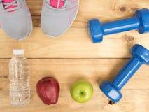 哑铃和鞋子炫耀用苹果和水瓶在木b 库存图片