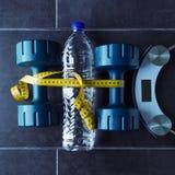 哑铃在一个瓶纯净的矿泉水和电镀物品旁边说谎 库存照片