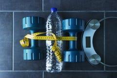 哑铃在一个瓶纯净的矿泉水和电镀物品旁边说谎 免版税库存图片
