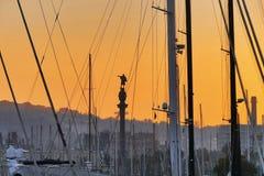 哥伦布雕象剪影视图通过小船的树和寿衣在口岸停泊了在日落巴塞罗那Catalunya 库存照片