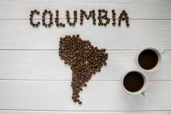 哥伦比亚的地图放置在与两个咖啡杯的白色木织地不很细背景的由烤咖啡豆制成 免版税库存照片