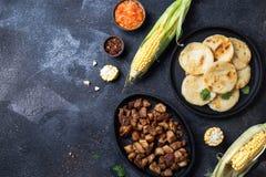 哥伦比亚的食物 玉米AREPAS和油煎的猪肉chicharron ans哥伦比亚的西红柿酱 顶视图 黑色背景 库存图片
