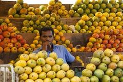 哥印拜陀,印度- 2015年6月28日:供营商在南印度被看见围拢了由各种各样的芒果在他的摊位 免版税库存图片
