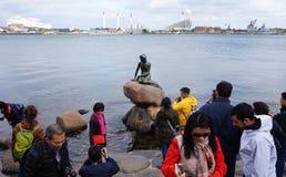 哥本哈根,丹麦- 2017年5月31日:为小的美人鱼的雕象的游人,小室沿海岩石的里尔Havfrue照相, 免版税库存图片