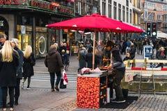哥本哈根- 2016年10月17日:在Nygade街上,街道客商油煎卖的有些通过坚果那些和的游人  免版税库存照片