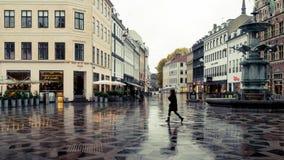 哥本哈根- 2016年10月22日:通过Amargertorv广场的妇女在小雨期间 库存图片