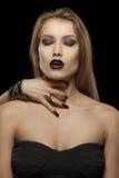哥特式妇女用吸血鬼的手她的脖子的 免版税图库摄影