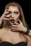 哥特式妇女用吸血鬼的手她的面孔的 库存图片