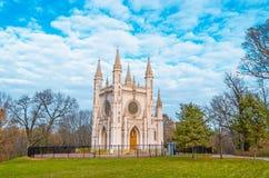 哥特式教会在有美丽如画的蓝天的秋天公园 免版税库存照片