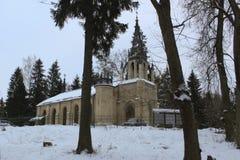 哥特式教会在雪冬天森林里 库存图片