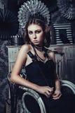 黑哥特式礼服的美丽的女孩与起来了 免版税库存照片