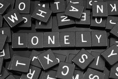 哥特式黑体字铺磁砖拼写词& x22; lonely& x22; 库存照片