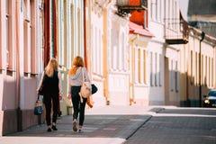 哥罗德诺,比拉罗斯 走在老传统房屋建设附近门面的两个少妇在晴朗的夏日在Hrodna, 免版税库存图片