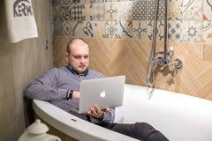 哥罗德诺,白俄罗斯- 2019年3月:年轻人雇员在与笔记本电脑的浴放置在现代豪华测量深度的商店 免版税图库摄影