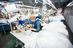哥罗德诺,白俄罗斯- 2013年12月13日:在纺织品工厂缝合与一台工业缝纫机的裁缝 库存图片