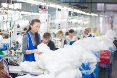 哥罗德诺,白俄罗斯- 2013年12月13日:在纺织品工厂缝合与一台工业缝纫机的裁缝 免版税库存图片